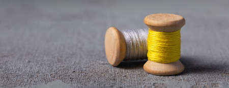 Trendy Illuminating Yellow and Ultimate grey colored threads wooden bobbins for stitching on concrete background banner