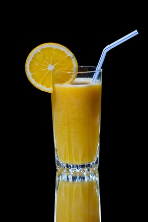 A glass of orange juice with reflection on black background photo