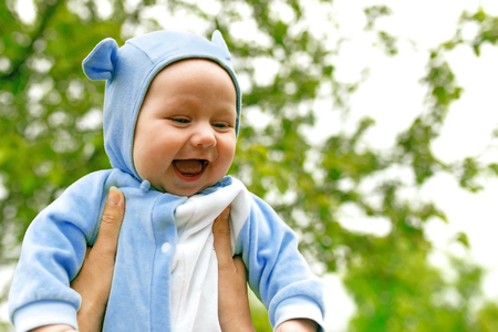 cute man: laughing baby on a background of trees
