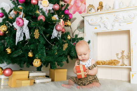 opens: child Christmas tree opens a gift Stock Photo