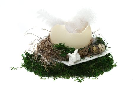 moos: Easter nest composition with two feathers in a big egg shell, a white ceramic plate, two smaller eggs, a white rabbit, dry twigs or grass and moos on white background