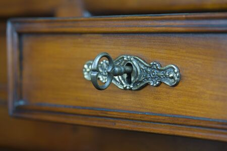 antique keyhole: Closeup of an antique keyhole with a key on a wooden drawer