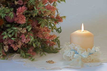 gold table cloth: Single candle in a wedding garter with a bouquet of dried flowers and two golden rings on festive embroidered white tablecloth Stock Photo