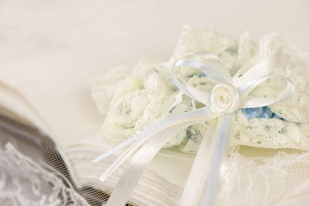 wedding guest: Blue and white wedding garter on a wedding guest book or photo album covered with an embroidered bridal wedding veil Stock Photo
