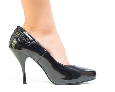 Girl foot on big shoe isolated on white photo