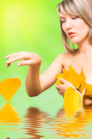 Portrait young woman with fall leafs in water photo