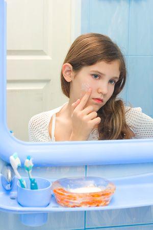 Teen girl in bathroom using cosmetic cream photo