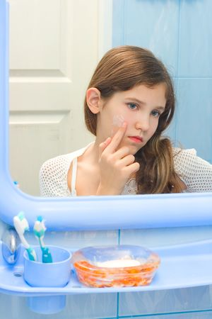 mirror on the water: Teen girl in bathroom using cosmetic cream