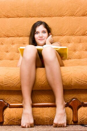 Teen girl reading book on sofa Stock Photo - 4976516