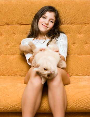 Teen girl with cat on the sofa photo