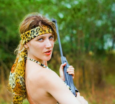 Woman with gun on nature photo