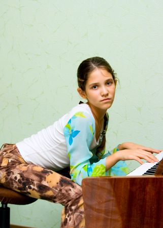 Portrait of cute teen girl and piano photo