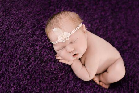 heir: Sleeping newborn baby girl on the background of purple carpet