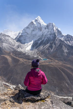 A woman sit and enjoy Ama Dablam mountain peak view in Everest region, Nepal, Asia