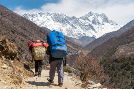 Porter carrying heavy loads walk to Everest base camp, Himalaya mountain, Nepal, Asia
