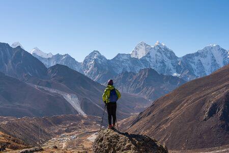 A trekker standing in front of Himalaya mountain range in Everest region, Nepal, Asia