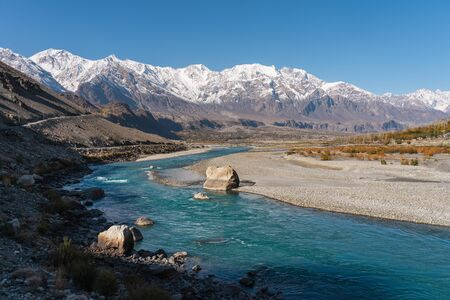 Beautiful blue and crystal clear water of Ghizer river in autumn season, Hindu Gush mountains range in Pakistan, Asia