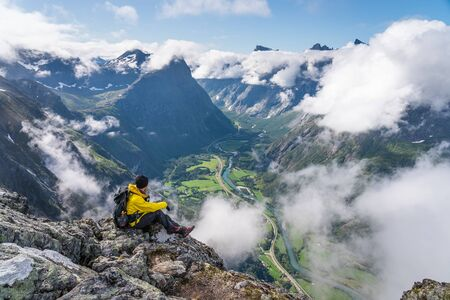 Young man traveller sitting and looking to mountains in Romsdalseggen hiking trail, Norway, Scandinavia, Europe Standard-Bild