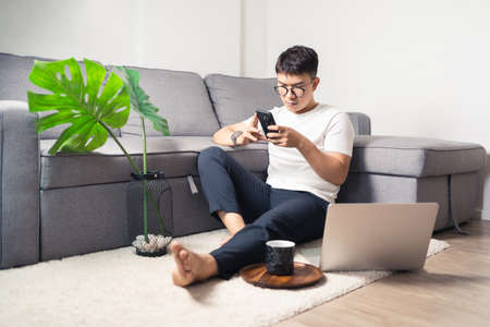 Young Asian man chatting with smartphone after working by using laptop computer. A man relaxing and sitting on floor in private room. Work from home concept. Bangkok Thailand