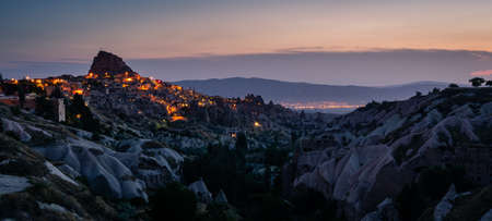 Panoramic landscape of Uchisar castle at night in Cappadocia, Central Anatolia, Turkey, Asia. Panoramic banner portion