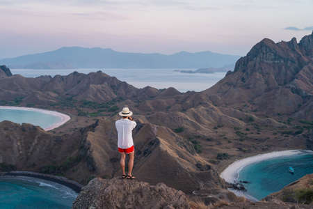 Young Asian man traveller standing and taking picture on top of Padar island in a morning sunrise, Komodo national park in Flores island in summer season, Indonesia, Asia