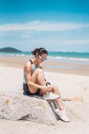 Asian young runner woman tying shoe laces. Sporty female runner getting ready for jogging on the beach in summer season, Pattaya, Thailand