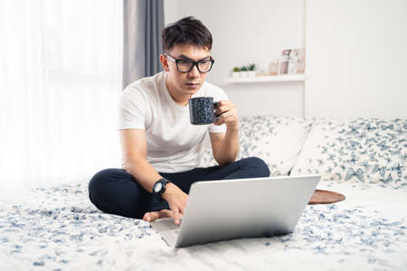 Young asian working at home wearing glasses. A man sitting on bed and working with laptop computer drinking a cup of coffee on bed. Work from home concept. Bangkok, Thailand Stock fotó