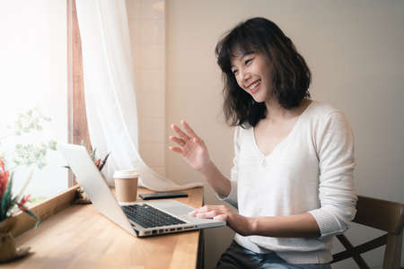 Young Asian woman working and video conferencing with laptop computer. A happy woman with smiley face working from home. A cup of coffee on wooden table. Work from home concept. Bangkok, Thailand