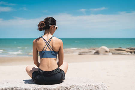 Portrait of young Asian woman with sitting on beach. Sporty female enjoying outdoor lifestyle in summer season. Bangkok, Thailand