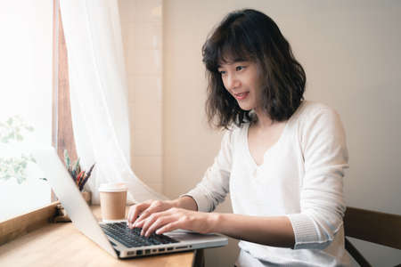 Young Asian woman working with laptop computer and drinking a cup of coffee. A happy woman with smiley face working from home. Social distancing concept. Bangkok, Thailand Stock fotó