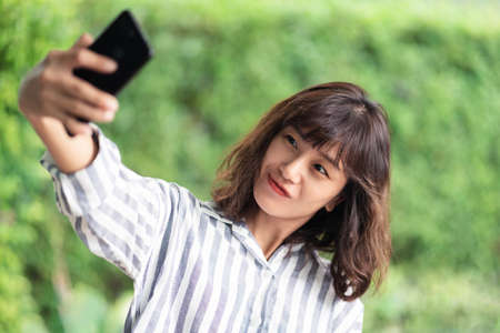 Young beautiful Asian woman using smartphone taking selfie photo. A happy girl enjoying outdoor lifestyle surrounded by greeny plant. Positive thinking concept. Bangkok, Thailand Stock fotó