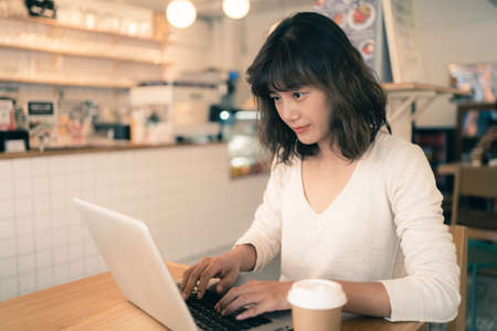 Young Asian woman working with laptop computer with a cup of coffee at a small coffee shop. Work from home and social distancing concept. Bangkok, Thailand