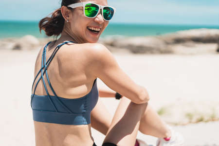 Young happy Asian woman with smiley face sitting on beach. Sporty female enjoying summer season. Pattaya, Thailand