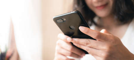 Close up hands of woman using smartphone chatting and searching information with blurry smiley face background. copy space of technology business and social distancing concept. Panoramic banner portion, Bangkok, Thailand Stock fotó