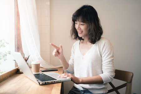 Young Asian woman working and video conferencing with laptop computer. A happy woman with smiley face working from home. A cup of coffee on wooden table. Social distancing concept. Bangkok, Thailand Stock fotó