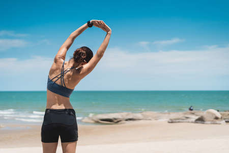 Young Asian sporty woman wearing sports wear and stretching on the beach. Female working out outdoor in summer season. Pattaya, Thailand