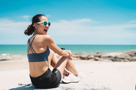 Young happy Asian woman with smiley face sitting on beach. A Sporty female wearing sport bra and enjoying summer season. Bangkok, Thailand Stock fotó