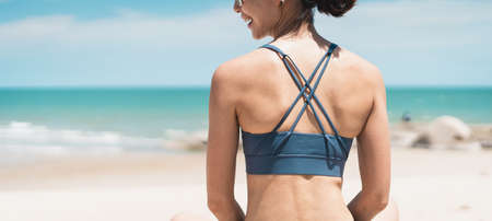Close up back of young Asian woman wearing sport bra sitting on beach. A Sporty female enjoying outdoor lifestyle in summer season . Bangkok, Thailand Stock fotó