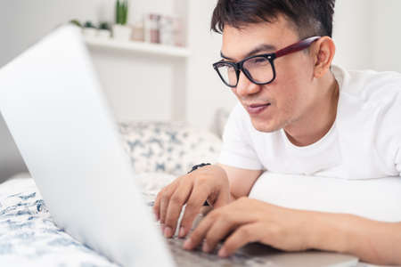 Close up of smiling Asian man wearing eyes glasses using laptop computer working from home laying on bed, digital lifestyle social distancing, work from home concept. Bangkok, Thailand