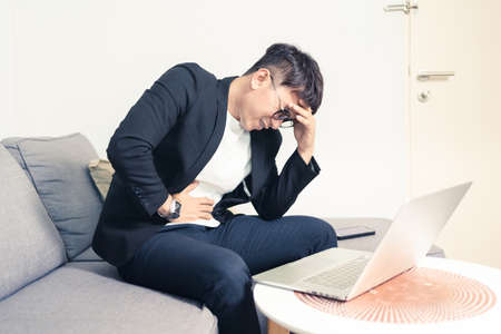 Young Asian business man sitting on sofa and working from home. Man feeling stress and suffering from office syndrome with headache. Tired young entrepreneur manager. Work from home concept. Bangkok, Thailand