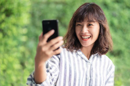 Young beautiful Asian woman using smartphone video chatting with another people. A happy girl enjoying outdoor lifestyle surrounded by greeny plant. Positive thinking concept. Bangkok, Thailand