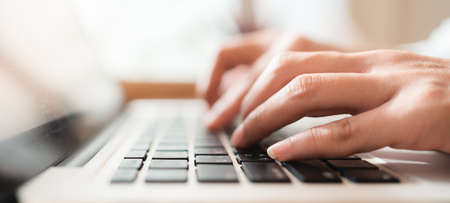 Close up hands of woman using laptop computer working and searching online information with blurry background. Technology business and social distancing concept. Panoramic banner portion. Bangkok, Thailand
