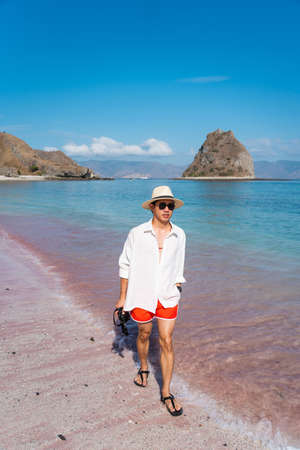 Young Asian man traveler wearing white shirt and walking on pink beach in Komodo national park. A man holding camera and enjoying summer season. Flores island in Indonesia, Asia