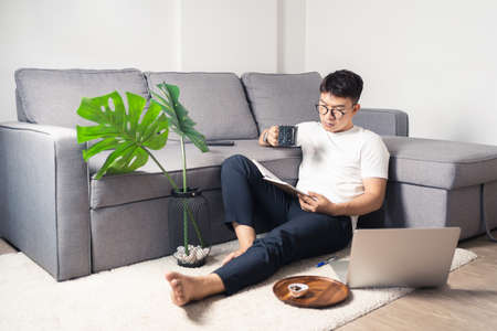 Young Asian man wearing eyes glasses and working from home and drinking coffee in a morning with laptop computer and notebook. Work from home concept. Bangkok, Thailand