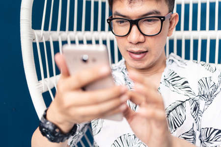 Young Asian man using smartphone for searching and checking information and communicated to another people. Social distancing concept. Bangkok, Thailand