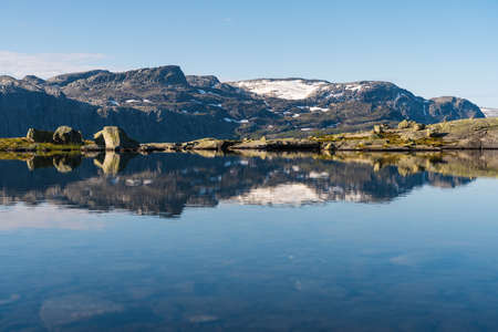 Beautiful reflection of mountains  between the way to Trolltunga cliff in Odda in a morning, western of Norway in summer season, Norway, Scandinavia, Europe Stock fotó