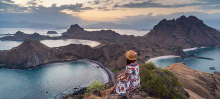 Young traveller sitting and relaxing on top of Padar island at sunset, Komodo national park in Indonesia, Asia. Panoramic banner portion