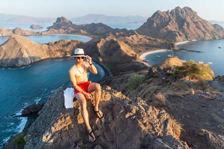 Young Asian man traveller enjoying beautiful morning sunrise. A man sitting on rock on top of Padar island in Komodo national park in summer season. Flores island in Indonesia, Asia
