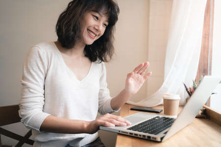 Young Asian woman working and video conferencing with laptop computer. A happy woman with smiley face working from home. A cup of coffee on table. Work from home concept. Bangkok, Thailand