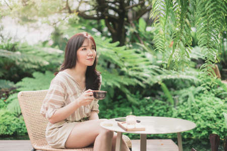 Young Asian woman sitting and relaxing in garden with a cup of coffee in a morning. A enjoying natural outdoor lifestyle. Bangkok, Thailand
